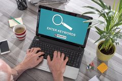Keywords search concept on a laptop. Man using a laptop with keywords search concept on the screen Stock Photo