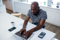 Man using laptop in kitchen Stock Images