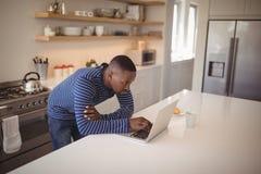 Man using laptop in kitchen Stock Photos