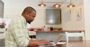 Man using laptop in kitchen 4k