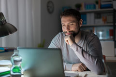 Man using a laptop late at night Stock Photography