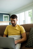 Man using laptop in living room Royalty Free Stock Image