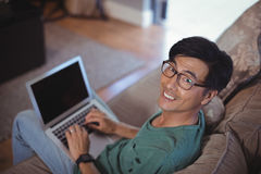 Man using laptop in living room Stock Image