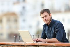 Man using a laptop and looking at camera in a balcony royalty free stock photos
