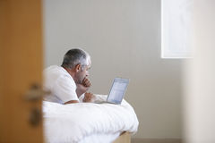 Man Using Laptop While Lying In Bed Royalty Free Stock Image