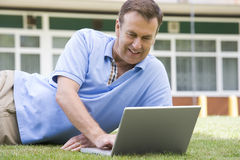 Man using laptop while lying in grass on campus.  Stock Photos
