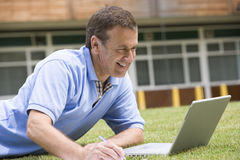 Man using laptop while lying in grass on campus.  Stock Images