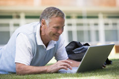 Man using laptop while lying in grass on campus.  Royalty Free Stock Images