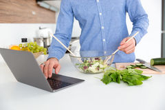 Man using laptop and making salad in glass bowl Stock Images