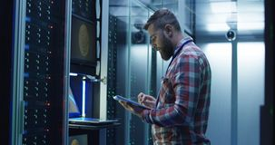 Man using laptop on mining farm in data center. Side view of modern IT engineer using tablet and laptop setting servers in data center while working on mining royalty free stock images