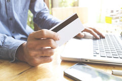 Man using laptop and mobile phone to online shopping and pay by credit card. Royalty Free Stock Image