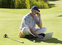 Man using a laptop and mobile phone whilst on the golf course Stock Image