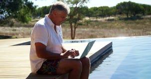 Man using laptop near poolside 4k. Man using laptop near poolside during safari vacation 4k stock footage