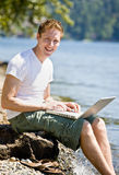 Man using laptop near water Stock Photos