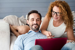 Man using laptop near woman on couch Royalty Free Stock Images