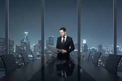 Man using laptop in office. Handsome young businessman using laptop computer in conference room interior with table, chairs and night city view. 3D Rendering Stock Photo