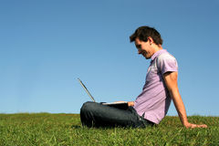 Man using a laptop outdoors Stock Photo