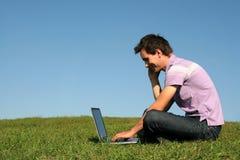 Man using a laptop outdoors. Young man using a laptop outdoors Royalty Free Stock Photos