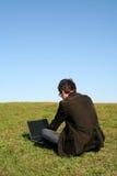 Man using a laptop outdoors. Young man using a laptop outdoors Stock Image