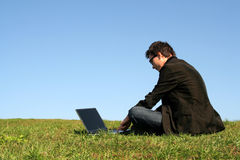 Man using a laptop outdoors. Young man using a laptop outdoors royalty free stock images