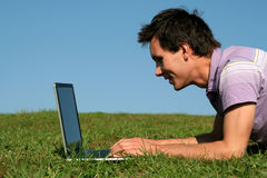 Man using a laptop outdoors. Young man using a laptop outdoors Stock Images