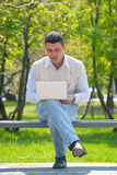 Man using a laptop outdoors Stock Images