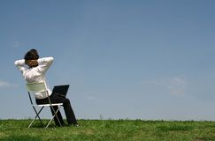 Man using laptop outdoors. Man sitting in chair outdoors stock images