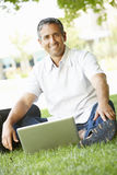 Man using laptop outdoors Stock Photography