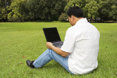 Man using a laptop outdoors Stock Photography