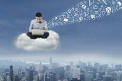 Man using laptop over cloud. Asian businessman working with his laptop over cityscape Royalty Free Stock Photography