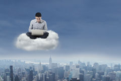 Man using laptop over cloud 1. Asian businessman working with his laptop over cityscape Royalty Free Stock Images