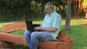 Man using laptop in the park on bench stock footage