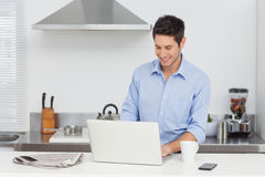 Man using a laptop pc in the kitchen Stock Photos