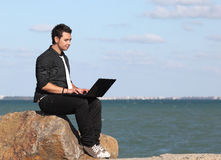 Man using laptop and phone at beach Stock Photography