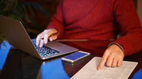 Man using laptop and pointing to a pressed sheet stock photos