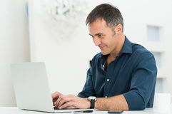 Man Using Laptop. Portrait Of A Happy Mature Man Using Laptop Stock Photo