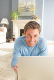 Man Using Laptop Relaxing Laying On Rug At Home Stock Photos