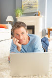 Man Using Laptop Relaxing Laying On Rug At Home Royalty Free Stock Photo