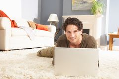 Man Using Laptop Relaxing Sitting On Rug At Home Royalty Free Stock Images