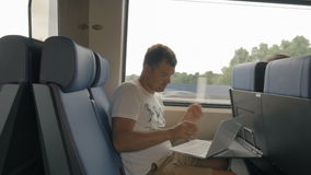 Man using laptop during ride in commuter train. Young man working with laptop while traveling by commuter train. Doing job or entertainment during railway stock video