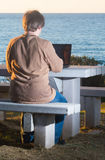 Man using laptop with sea view Royalty Free Stock Photo