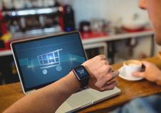 Man using Laptop with Shopping trolley icon Stock Photography