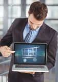 Man using Laptop with Shopping trolley icon Stock Photo