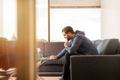 Man Using Laptop Sitting on Couch stock image