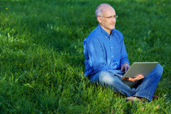 Man Using Laptop While Sitting On Grass. Mature man using laptop while sitting on grass in park Stock Photo