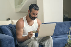 Man using a laptop while sitting on a sofa in his living room Stock Image