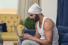 Man using a laptop while sitting on a sofa in his living room Stock Photos