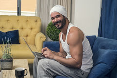 Man using a laptop while sitting on a sofa in his living room Stock Images