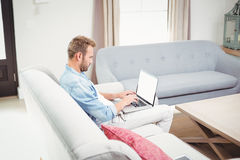 Man using laptop while sitting on sofa in living room Stock Photos