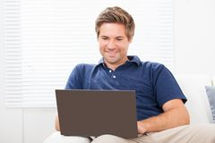 Man using laptop on sofa at home Royalty Free Stock Images